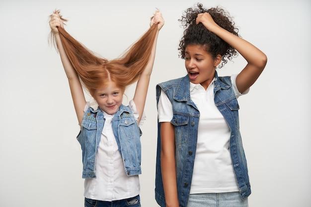 어두운 피부 갈색 머리 아가씨 미소와 함께 흰색에 서있는 동안 그녀의 긴 머리를 가진 재미 사랑스러운 밝은 빨간 머리 여자 아이의 실내 초상화