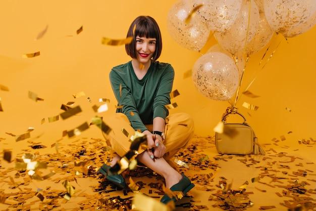 紙吹雪の上に座っている楽しいブルネットの少女の屋内肖像画。緑のセーターのポーズで陽気なヨーロッパの女性。