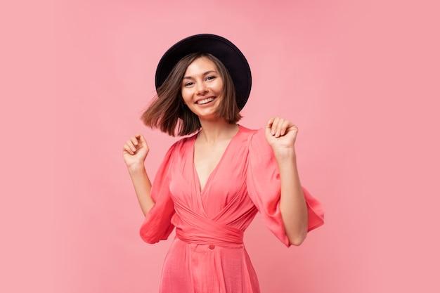 핑크 드레스에 즐거운 매력적인 여자의 실내 초상화. 춤과 웃음 행복 젊은 아가씨.