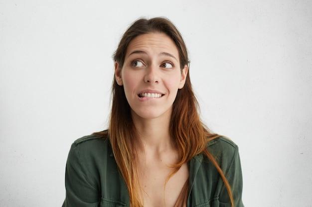 Портрет застенчивой симпатичной женщины в помещении, которая смущенно прикусывает нижнюю губу, хочет что-то сказать, но не имеет смелости сделать это. женщина, чувствуя свою вину, выглядит смущенной