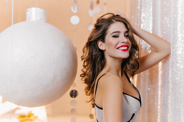 Крытый портрет стройной бледной девушки с красивой улыбкой, играющей с темными вьющимися волосами. очаровательная модная женщина в белом платье позирует на вечеринке с огромной рождественской игрушкой.