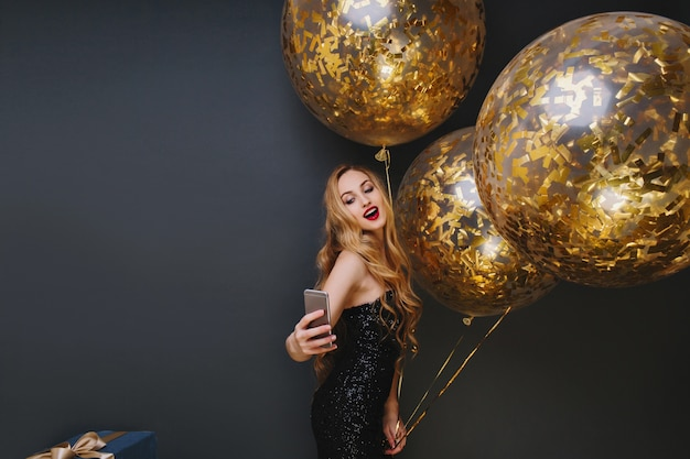 お祝いでselfieを作る見事な金髪の女の子の屋内ポートレート。楽しいと自分の写真を撮るパーティー風船を持つ壮大な女性。