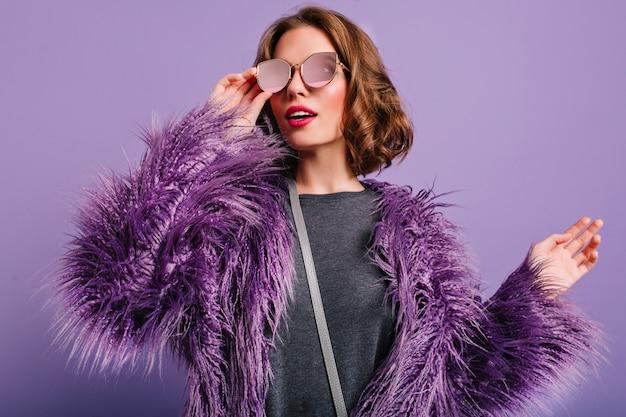 Крытый портрет стильной европейской женской модели в очках позирует на фиолетовом фоне