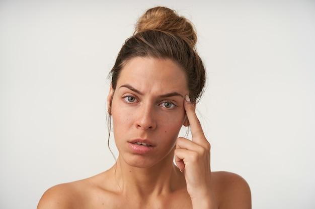 カジュアルな髪型、眉をひそめ、彼女の寺院に人差し指を保ち、白で隔離の疲れた若い女性の屋内肖像画