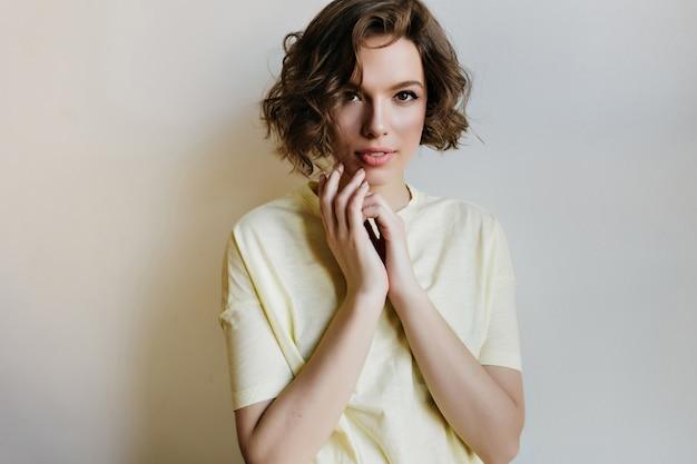 白い壁に隔離された薄い肌を持つ魅力的な若い女性の屋内の肖像画。かわいいtシャツに興味のある白人の巻き毛の女の子。