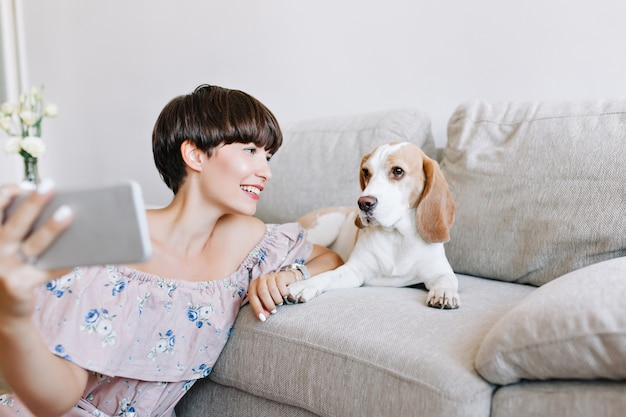 ソファに横になっているビーグル犬とselfieを作る素晴らしい黒髪の少女の屋内肖像画