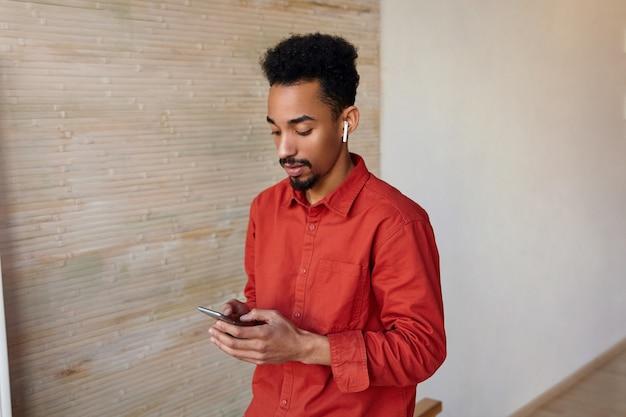 Крытый портрет молодого бородатого темнокожего мужчины с короткой стрижкой в красной рубашке, стоящего на бежевом интерьере со смартфоном в руках