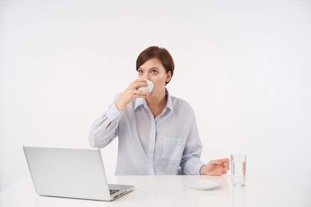 Крытый портрет молодой кареглазой короткошерстной брюнетки с естественным макияжем, пьющей кофе во время работы в современном офисе со своим ноутбуком, изолированной на белом