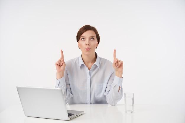 Портрет молодой кареглазой коротко стриженной дамы с естественным макияжем, держащей руки на столешнице и показывающей вверх указательными пальцами, в синей рубашке, сидя на белом