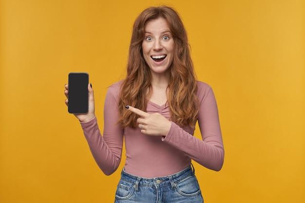 Портрет молодой рыжей самки в помещении, указывая пальцем на пустой дисплей своего телефона с удивленным, шокированным выражением лица