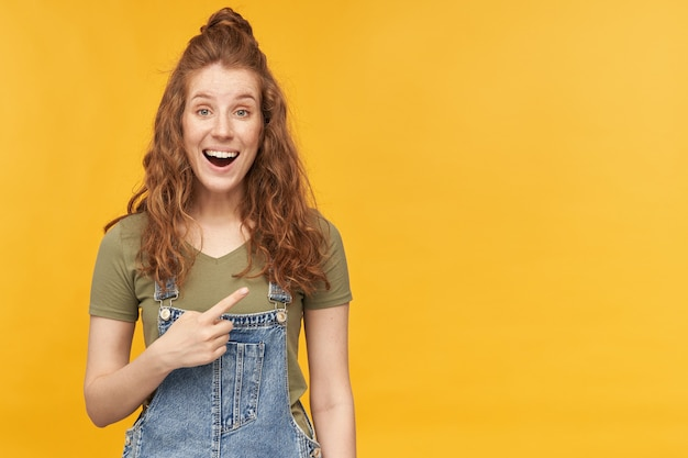 青いデニムのオーバーオールと緑のtシャツを着た若い生姜の女性の屋内ポートレートは、コピースペースで指の笑顔と喜ばしい表情で広く示されています。黄色の壁に隔離