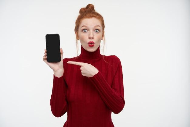 そばかすのある若い生姜の女性の屋内の肖像画は、白でショックを受けた、驚いた表情で彼女の携帯電話の空白のディスプレイに指を指しています