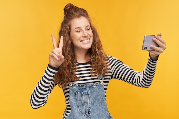 若い幸せな女性の屋内肖像画、剥ぎ取られたシャツを着て、デニムのオーバーオールは、隔離中に彼女のボーイフレンドとビデオチャットをしながらvサインを示しています