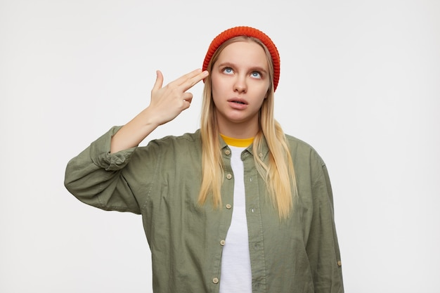 Портрет молодой красивой блондинки в помещении, складывающей пистолет рукой и поднимающей его к голове, закатывая глаза, изолированной на синем в повседневной одежде