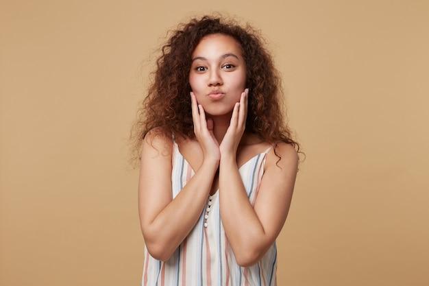베이지 색에 고립 된 긍정적으로 보면서 제기 손으로 그녀의 뺨을 만지고 입술을 추구하는 젊은 예쁜 갈색 머리 곱슬 여성의 실내 초상화