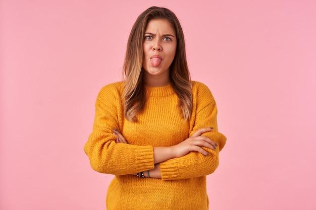 젊은 예쁜 갈색 머리 여성의 실내 초상화 그녀의 가슴에 손을 접고 분홍색에 포즈를 취하고 눈썹을 찌푸리고 혀를 보여주는 동안 속이는