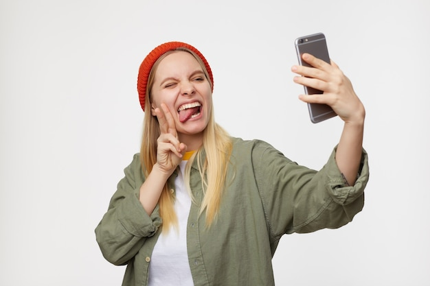彼女のスマートフォンでselfieを取り、平和のジェスチャーを示している間、変な顔をしている赤い帽子をかぶった若いかわいい白い頭の女性の屋内肖像画、青で隔離