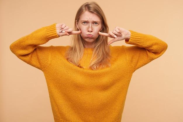 ベージュの上に立って、口に空気を取り入れながら彼女の頬に人差し指を保持しているナチュラルメイクの若い赤毛の女性の屋内肖像画