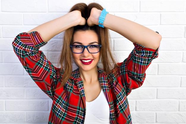 若いおしゃれなセクシーな女性の屋内ポートレート、軽薄なポニーテールを着て、クレイジーになって、楽しんで、流行に敏感な透明なメガネを着て笑っています。