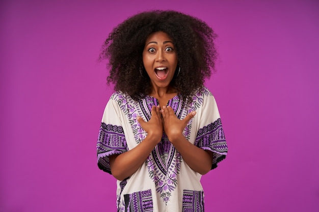 Indoor portrait of onjoyed young curly dark skinned female in casual clothes folding palm on her chest happily with wide eyes and mouth opened, isolated on purple