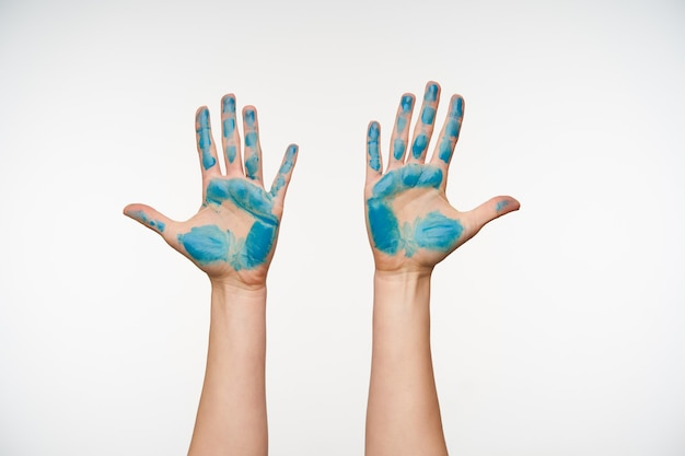 Indoor portrait of painted young woman's hands being raised while showing palms with all fingers apart, isolated on white. human gesturing concept