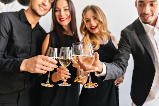 Indoor portrait of people clink glasses with guys in black attires