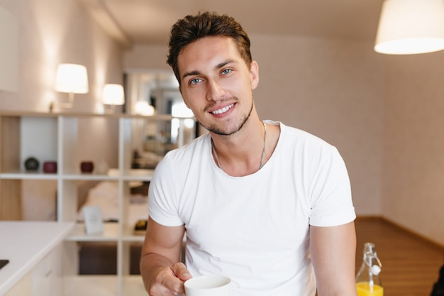 Indoor portrait of pleased brunette man with beard posing with cup of tea in his apartment