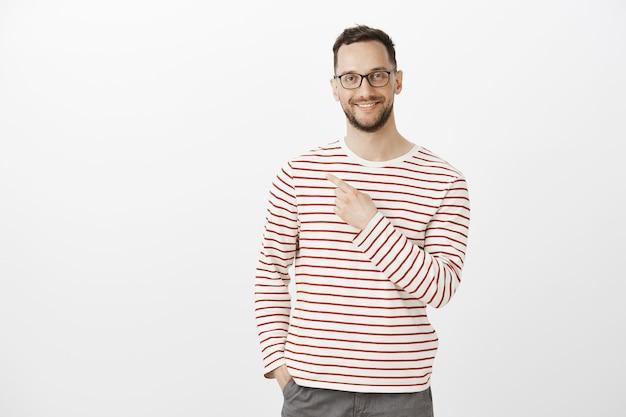 Ritratto dell'interno del modello di uomo di bell'aspetto soddisfatto con gli occhiali, che sorride ampiamente e punta indietro o nell'angolo in alto a sinistra