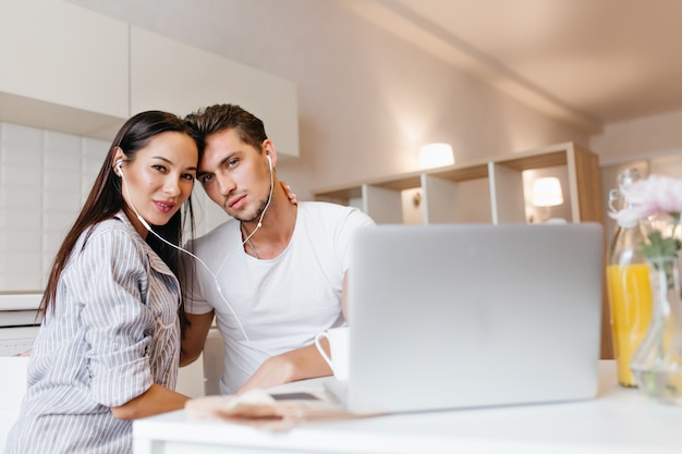 Ritratto dell'interno della coppia sposata felice che trascorre insieme la mattina di fine settimana e che utilizza computer portatile