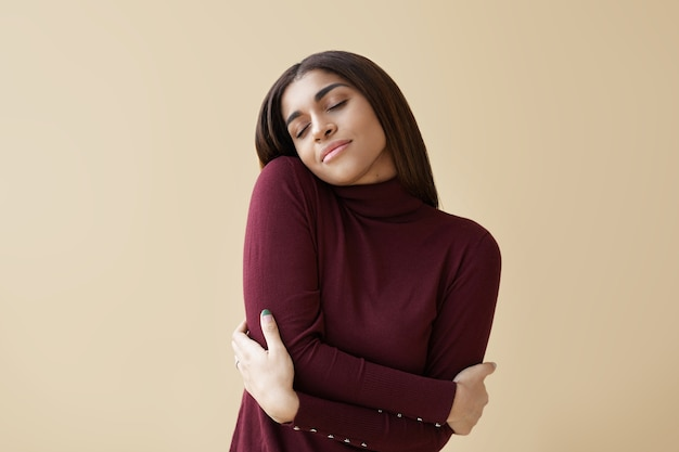 Indoor portrait of positive relaxed young mixed race brunette woman closing eyes with pleasure, keeping arms around herself, enjoying soft fabric of her new maroon cashmere turtleneck sweater