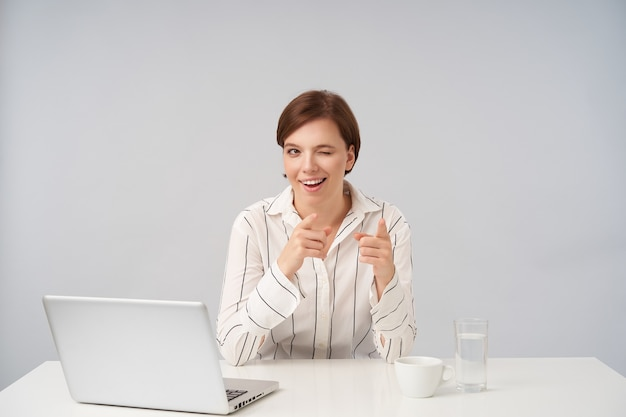 Indoor portrait of positive young brown haired lady with natural makeup winking cheerfully and pointing aside with raised forefingers, sitting on white