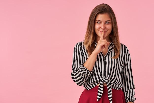 Ritratto dell'interno di positivo giovane bella donna castana alzando la mano con gesto di silenzio mentre si fida di qualcuno il suo segreto, indossa una camicia a righe e gonna rossa sul rosa