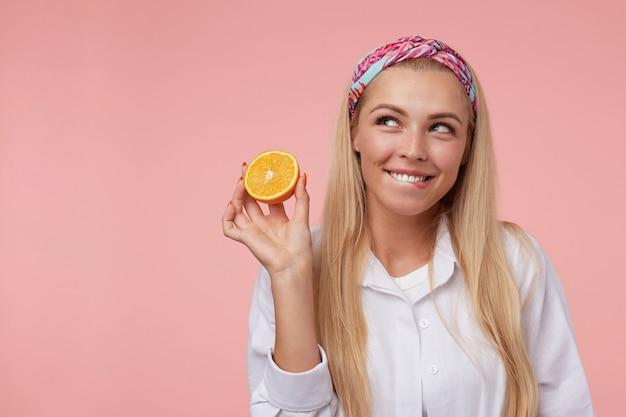 Ritratto interno di piuttosto giovane donna con lunghi capelli biondi, indossa fascia colorata e camicia bianca, morde un labbro e tiene in mano metà dell'arancia