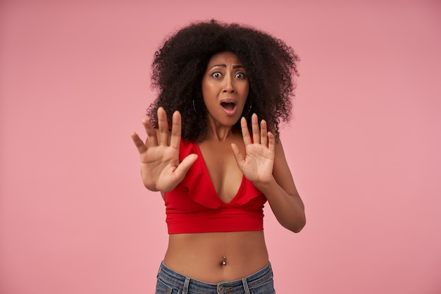 Indoor portrait of scared dark skinned woman with belly button piercing posing on pink fearfully and raising hands in stop gesture