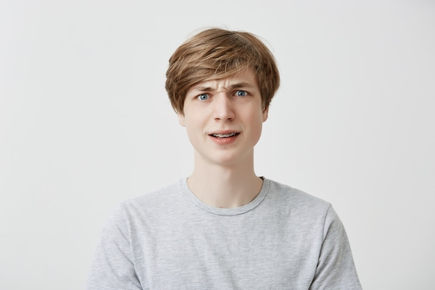 Indoor portrait of serious dissatisfied puzzled emotional fair-haired young man with braces, frowns his face in bewilderment, reacts on teachers`s remark. peope and reaction concept