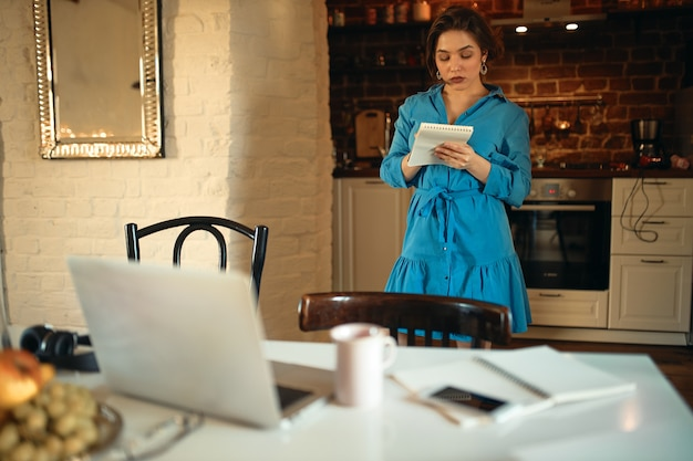 Indoor portrait of serious young woman in blue dress standing in kitchen with notebook