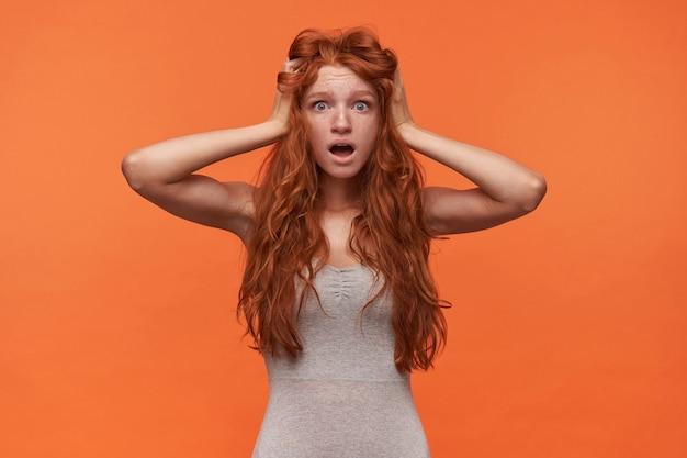Ritratto dell'interno di scioccato attraente giovane donna rossa con i capelli ondulati lond in piedi su sfondo arancione, stringendo la testa con la bocca larga aperta e occhi arrotondati
