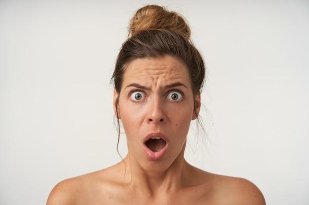 Ritratto dell'interno di giovane donna scioccata con acconciatura casual, in posa con la faccia sorpresa, guardando con la bocca e gli occhi spalancati