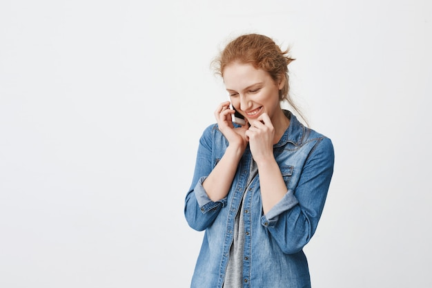 Indoor portrait of shy cute college student with ginger hair combed in bun talking on smartphone and being confused or embarassed speaking with guy he likes