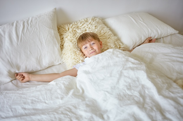 Indoor portrait of sleepy european teenage boy stretching arms after awakening early in the morning, lying on white bedclothes, going to school, looking , having lazy facial expression