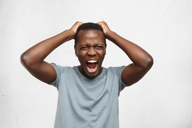 Indoor portrait of stressed fed-up afro-american male dressed in grey t-shirt holding hands on head and screaming loudly in despair and anger, furious with noise coming from apartment above him