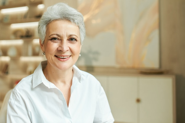 Indoor portrait of successful middle aged businesswoman with short gray hair working at her office
