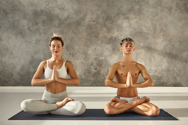 Indoor portrait of two barefoot young people man and woman with flexible strong bodies meditaing on one mat during yoga class, sitting in lotus posture, closing eyes and holding hands in namaste