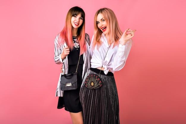 Ritratto interno di due donne sorelle migliori amiche felici, che indossano abiti alla moda in bianco e nero e capelli rosa, abiti femminili da sera glamour, atmosfera di festa