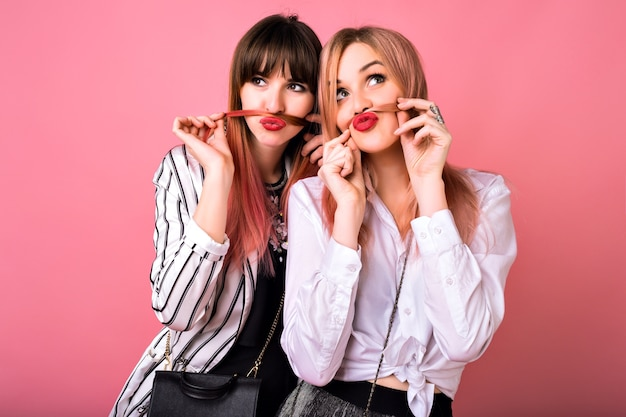 Indoor  portrait of two happy best friends sisters women, wearing trendy black and white clothes and pink hairs, hugs and smiling, exited emotions, hipster style