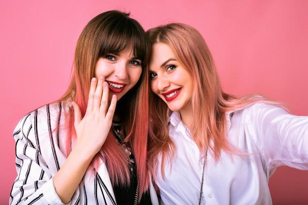 Ritratto dell'interno di due donne felici delle sorelle migliori amiche, che indossano abiti alla moda in bianco e nero e capelli rosa, facendo selfie, godendosi il tempo insieme