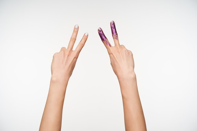 Indoor portrait of two raised female's pretty hands with white manicure forming victory gesture with fingers while being isolated on white