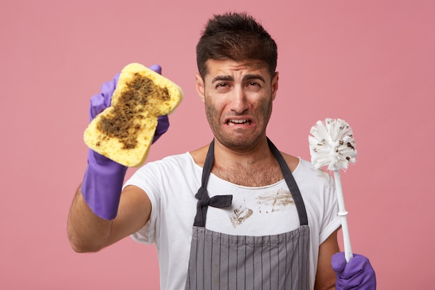 Indoor portrait of unhappy crying young bearded man in apron and rubber gloves feeling sad and upset as he has to do cleaning up in apartment, holding sponge and toilet brush, having unwilling look