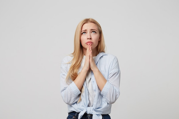 Indoor portrait of worry sad attractive young blond female in blue shirt and jeans standing with palm hands, praying and looking at up, hoping for better in life
