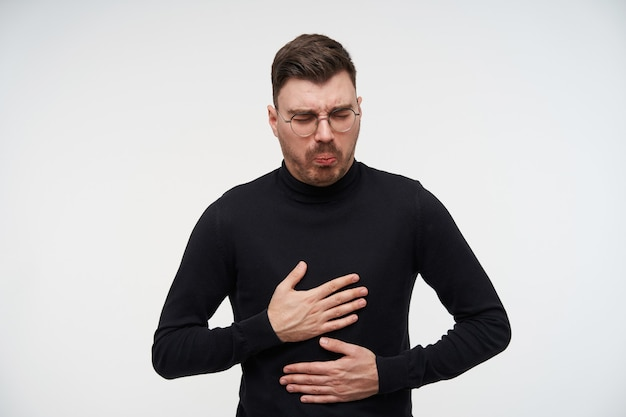 Indoor portrait of young bearded brunette man with short haircut holding palms on his stomach and grimacing his face, feeling sick while posing on white